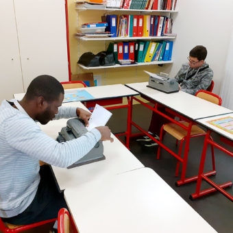 Jeunes en classe avec les machines à écrire en Braille